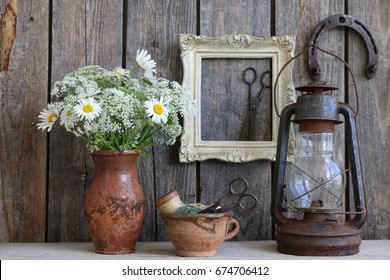 Bouquet of flowers in old authentic clay, ceramic pot, vase, rustic scissors in golden ton wooden rectangular frame, wooden spool in pottery mug, cup, rusty oil lamp, farmhouse style, daylight