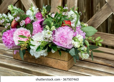 Bouquet of flowers in old wooden rustic box. Selective focus, close up.