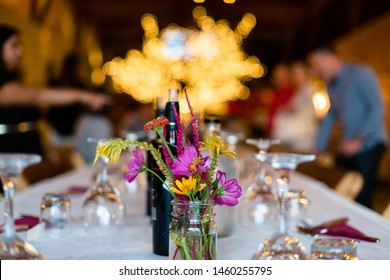 Bouquet of flowers on a beautifully decorated dinner table with glassware, cutlery and napkins on a white tablecloth set for a grand party.