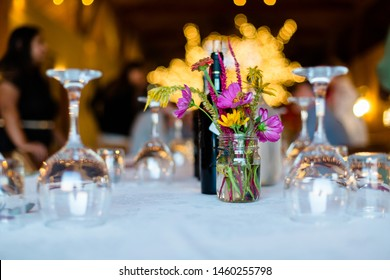 Bouquet of flowers on beautifully decorated dinner table with glassware, cutlery and napkins on white tablecloth set for a grand party.