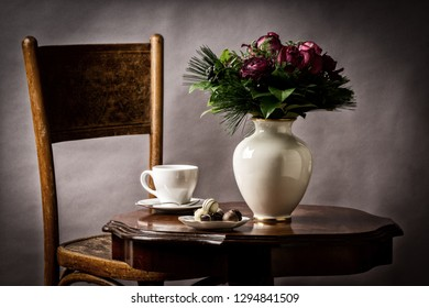 bouquet of flowers, on old coffee-table with old chair and old antique vase and  chocolates