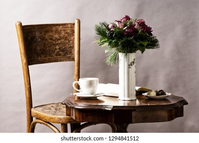 bouquet of flowers, on old coffee-table with old chair and book