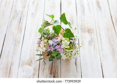 Bouquet of flowers on a old light shabby chic wooden background. Place for text.