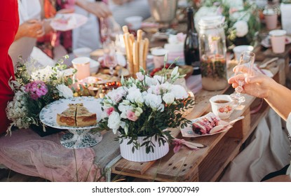 a bouquet of flowers on a table from pallets. celebrating with friends and family in a park or garden. outdoor picnic. festive boho wedding table