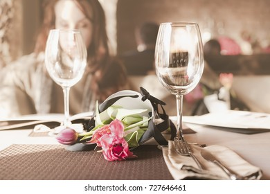 a bouquet of flowers on the table in the restaurant and the girl reads the menu in the background