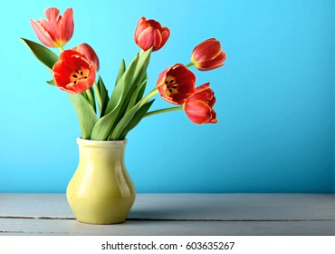 bouquet flowers tulips vase white wooden table blue background