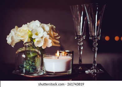 Bouquet of flowers in a vase, candles and champagne glasses on a tray, vintage home decor on an a table, dark tones