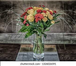 a bouquet of flowers with yellow roses, red gerberas and cloves