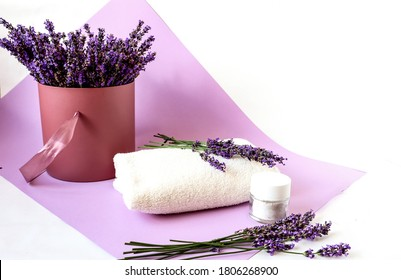 Bouquet of fragrant lavender flowers in a vase with a white bath towel and body cream, close-up, lilac background, place for the inscription