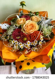 Bouquet of fresh flowers with roses. Warm sunny summer colors.