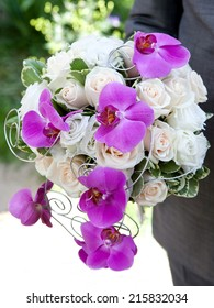 Bouquet of fresh flowers for the wedding ceremony. Bouquet of orchids, roses and other flowers in the groom's hands closeup.