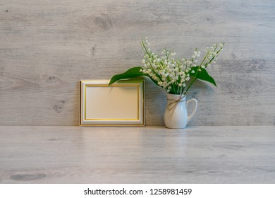 Bouquet of fresh lilies of the valley flowers and empty photoframe on light wooden background. Beautiful spring still life, mock up for greeting card, good morning concept