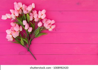 Bouquet of fresh pink flowers on a matching vibrant pink wood background with copy space for your greeting or wishes to a loved one