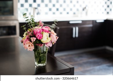Bouquet of fresh pink flowers on the dining table in the interior of modern kitchen