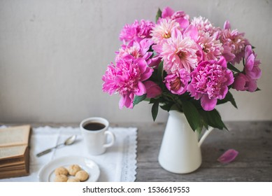 Bouquet of fresh pink peonies in a white enameled jug, Old book, cup of coffee and homemade cookies on a plate on gray wooden background - Shutterstock ID 1536619553