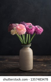 Bouquet of fresh ranunculus flowers in a vase, moody light