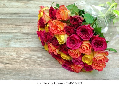 bouquet of fresh roses on a wooden background close-up. horizontal photo.