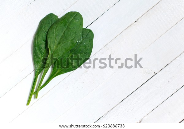 A bouquet of fresh spinach on a wooden table