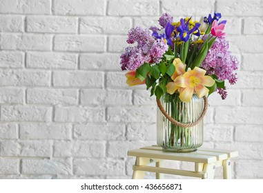 Bouquet of fresh spring flowers on brick wall background