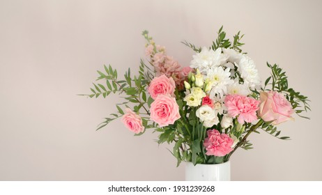 Bouquet of fresh spring flowers in vase on light pink wall background, copy space.  Minimalism home decor concept