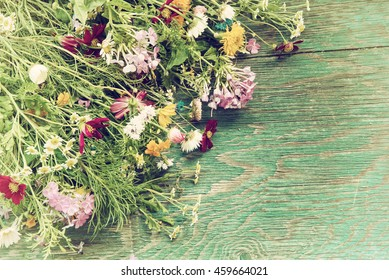 Bouquet of fresh summer flowers on the blue wooden grunge desk. Mock up for greeting cards, holiday postcards, invitation in vintage hipster eco rustic style with copy space
