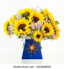 A bouquet of fresh sunflowers in a hand-decorated cardboard box. Decorative quiling on a box.