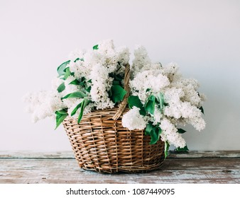 Bouquet of fresh white lilac flowers in wicker basket on wooden