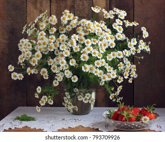 Bouquet of garden daisies and strawberries on the table with a lace tablecloth. Still life in rustic style.