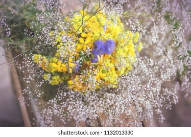 Bouquet of garden flowers and healing herbs on old wooden rustic table. Close up, shallow depth of the field, toned.