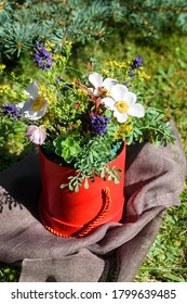 A bouquet of garden flowers ina red vase on a brown napkin on the grass.Vertical orientation.