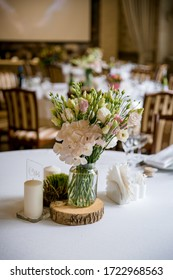 a bouquet of garden white flowers in a glass jar on a table with a white tablecloth on a tree cut, around white thick candles