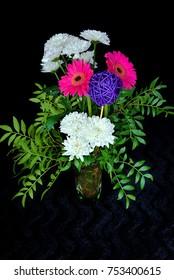 Bouquet in a glass vase on black velvet
