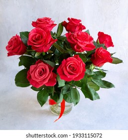 A bouquet of gorgeous red roses in a vase on a light gray background. Flowers as a gift.