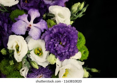 bouquet of green chrysanthemum, white eustoma, violet eustoma, purple orchid on a black background on the left side close-up