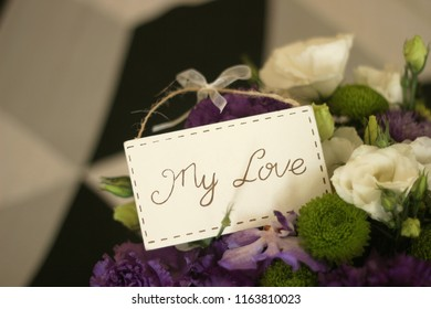 bouquet of green chrysanthemum, white eustoma, purple eustoma, purple orchid on black and white background side to the right close-up inscription my love