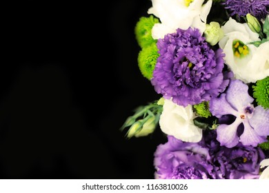 bouquet of green chrysanthemum, white eustoma, purple eustoma, purple orchid on a black background on the right side