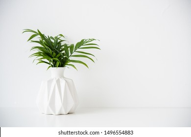 Bouquet of green palm leaves in white ceramic vase