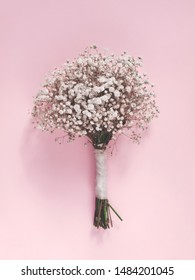 Bouquet of gypsophilia flowers isolated on light pink background. Flat lay. Top view