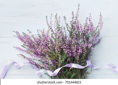 Bouquet of heather (calluna vulgaris, erica, ling) decorated satin ribbon on blue vintage background from above. Beautiful pink flower for greeting card.