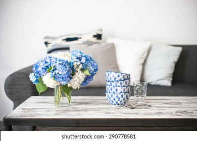 Bouquet of hortensia flowers and glass bowls on modern wooden coffee table and cozy sofa with pillows. Living room interior and home decor concept