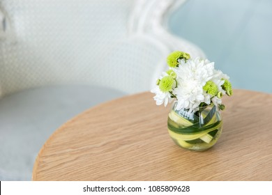 Bouquet of hortensia flowers on modern wooden coffee table and cozy sofa with pillows. Living room interior