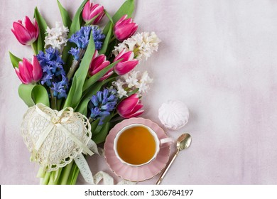 bouquet of hyacinths and tulips, a cup of tea, marshmallows and a heart of lace on a pink background