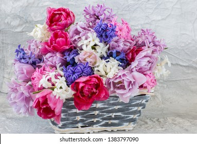 bouquet of hyacinths and tulips in a wicker basket