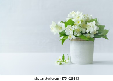 a bouquet of jasmine flowers in a vase on the table close-up. a bouquet of white jasmine flowers on a white background. holiday card with jasmine flowers.