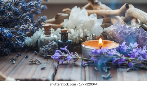 Bouquet of lavender, driftwoods, lighted candle and tiny glass bottles on a wooden background. Alternative medicine, aromatherapy, Wicca, Boho or esoteric background.