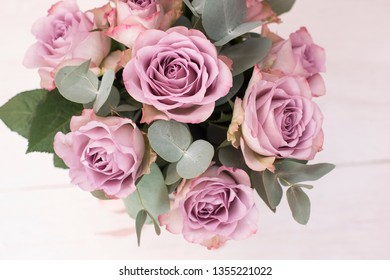bouquet of lavender roses on a white wooden background. Bouquet of roses and eucalyptus. Wedding festive bouquet on a white background. Violet roses.