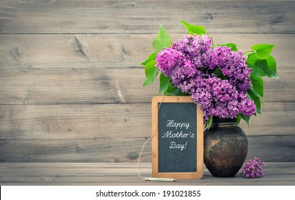 bouquet of lilac flowers in vase on wooden background. blackboard with sample text Happy Mother's Day! retro style toned picture