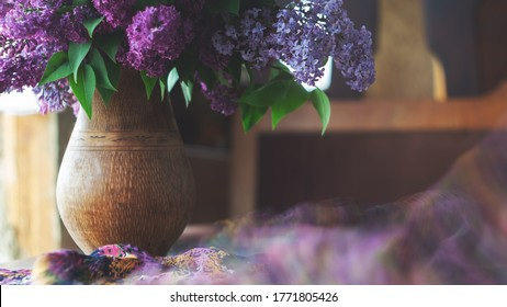 Bouquet of lilac in a jug and a silk scarf on a black wooden table. Retro style