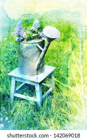 A bouquet of lilac in a metal watering can on grass background/vintage nature flower background with watercolor effects/Old, rusty watering can with liliac standing in grass