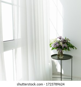 Bouquet of lilacs on a white balcony among white curtains